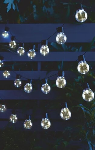 3 rows of warm white outdoor fairy lights in garden at night.