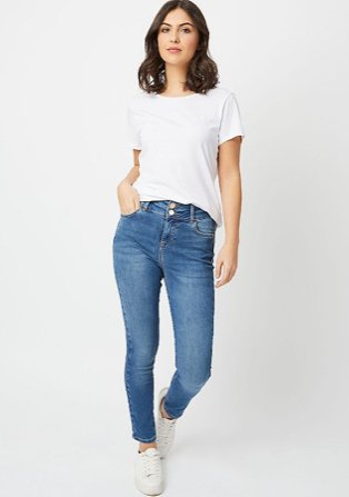 Woman wearing a white t-shirt and light blue skinny jeans and white trainers