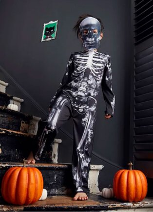 Child wearing halloween skeleton black and white halloween costume, with one pumpkin either side of him.