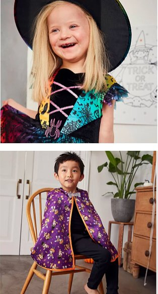 Child wearing witches hat and colourful halloween costume. Child sitting on a chair wearing black jeans, black t-shirt and a printed purple and orange cape.