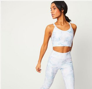 Woman wearing matching white sports bra and sports leggings