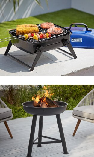 Small black BBQ with a blue lid, cooking an assortment of kebabs, burgers and corn on the cob. Black firepit on a deck next to a pair of outdoor armchairs.