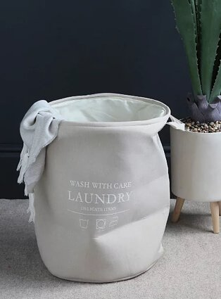 Light grey slogan laundry basket with artificial plant in the background.