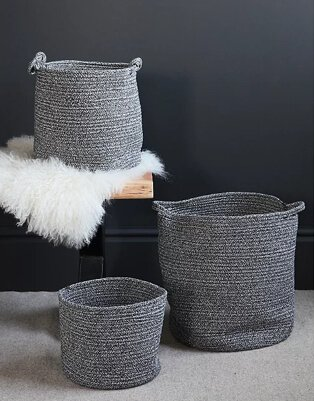 Medium grey storage basket on wooden seat and white faux fur rug with coordinating small and large baskets on the floor.