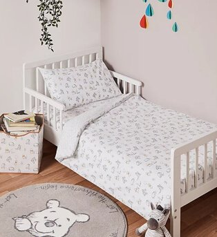 Kids bedroom features white cot bed with Disney Winnie the Pooh print duvet set with matching round rug and storage box.