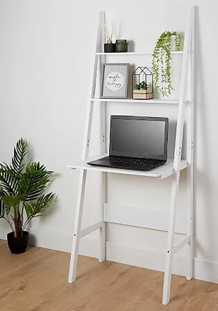 White ladder desk with green diffuser set, artificial plant, 'be happy' print, artificial plant in wire house and open laptop.