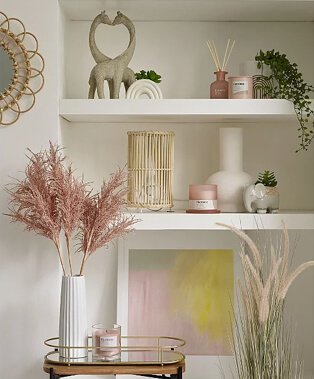 Two shelves topped with giraffe ornament, reed diffuser, rainbow artificial plant, wicker lamp, white vase, elephant artificial plant and green, pink and yellow framed print.