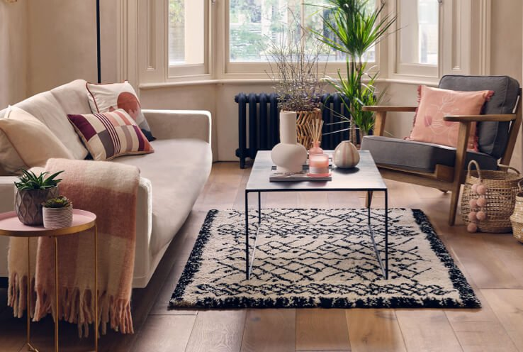 Large living room with natural sofa and grey armchair topped with cream, brown and pink scatter cushions with coffee table in the centre topped with artificial plant, cream vase, stripe vase and pink reed diffuser.