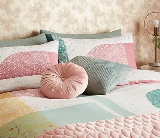 Double bed with multi-coloured pastel pattern with pink and green decorative cushions and pink quilted throw