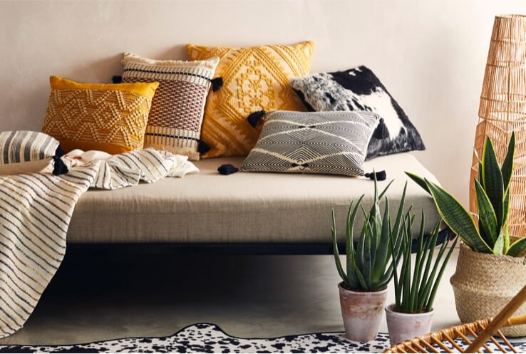 Sofa with an assortment of yellow, grey and black pillows, next to a large rattan floor lamp and several small artificial plants