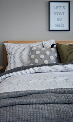 Double bed with wooden headboard and white and grey printed duvet, grey textures throw and grey and white polka dot and olive-green scatter cushion with black framed 'let's stay in bed' print hanging above.