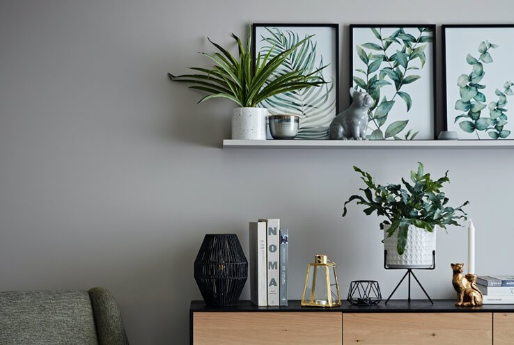 Grey wall with shelf holding plant, candle and grey bulldog ornament with three framed leaf prints leaning against wall, wood and black surface with books, gold and black candle holders, plant and brass tiger candle holder.