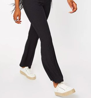 Legs of woman wearing black ribbed seam front kick flare trousers and cream lace-up pumps.