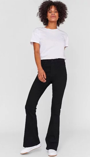 Woman poses wearing black ribbed kick flare trousers, white boxy t-shirt and white lace-up pumps.