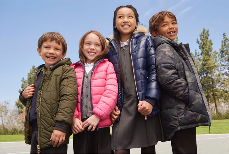 A group of four children standing in a playground wearing a variety of different padded coats over their school uniforms