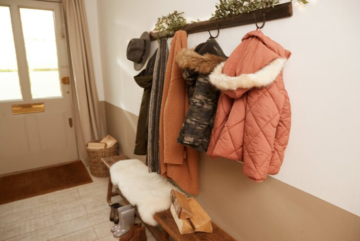 Cream and brown hallway with white door and wooden hanging rack with pink quilted parka, camo printed parka, pink textured coat, scarf and khaki hooded coat.