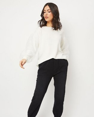 Woman wearing a white jumper with black joggers