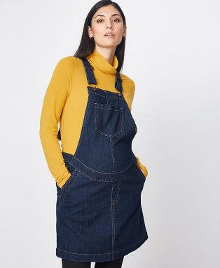 A pregnant woman wearing a dark blue pinafore dress over a mustard yellow roll neck top.