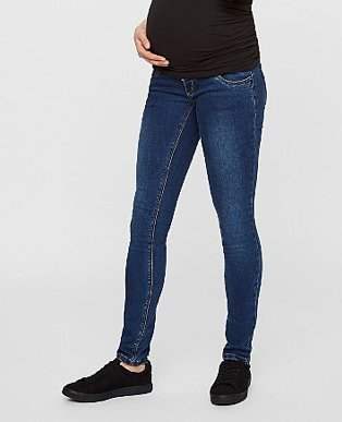 A pregnant woman wearing dark wash denim jeans with a black top and black trainers.