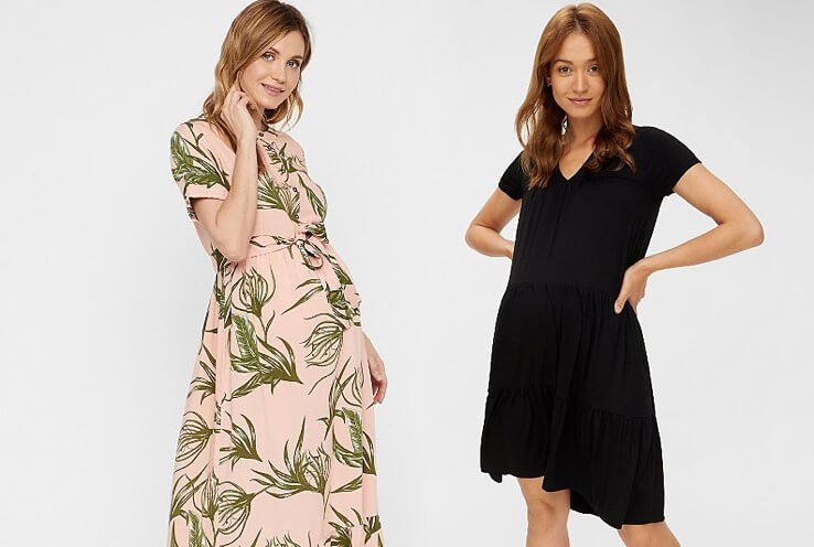 Two pregant women standing beside each other, one wearing a pink leaf print dress and the other wearing a black dress.