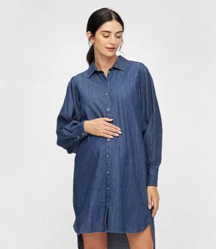 A pregnant woman standing with her hand on her bump wearing a Pieces denim shirt dress.
