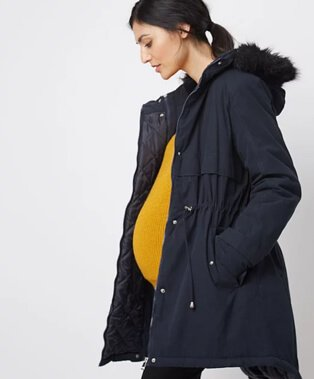 A pregnant woman wearing a navy faux fur trim hooded parka over a yellow jumper and black trousers.