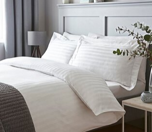 Double bed with white striped bedding