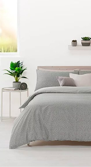 Double bed features green printed duvet set, mocha and cream scatter cushions with side table topped with artificial plant in white room with window in the background.