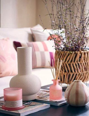 Cream living room features natural sofa with pink and cream scatter cushions with coffee table topped with artifical plant in wicker basket, cream vase, pink candle and reed diffuser set, selection of books and pink and cream stripey vase.