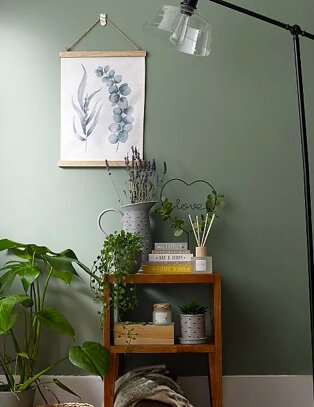 Green room features wooden table with assortment of books, artificial plants, heart-shaped ornament, candle and reed diffuser set, large jug with floor lamp to one side and leaf printed hanging frame in the background.
