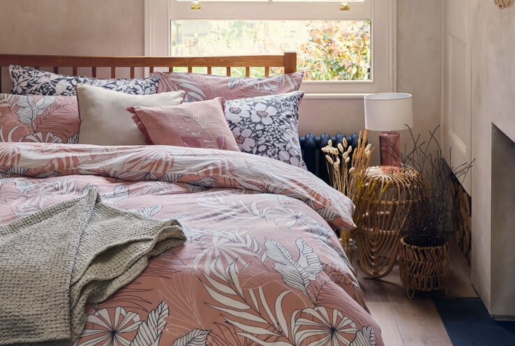 Double bed with wooden headboard features pink floral print duvet set with blue and while cushions next to rattan side table topped with pink lamp with cream shade.