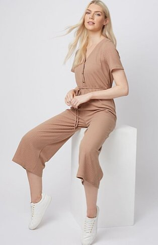 Woman wearing a short sleeve dusty pink jumpsuit with white trainers