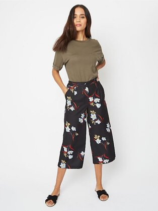 Woman wearing a khaki t-shirt with navy patterned floral culottes and black sandals