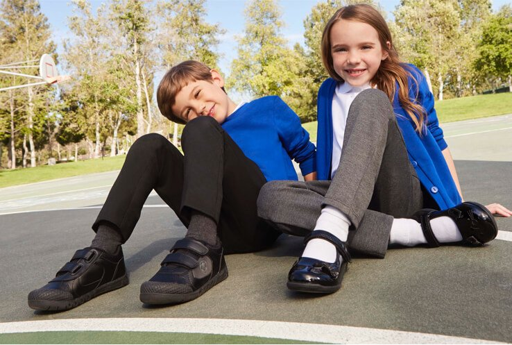 Two children in blue school jumpers and cardigans with grey school trousers and black school shoes