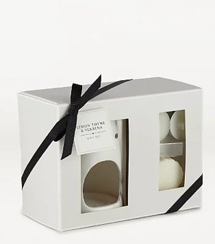 White candle and oil burner set with black gift bow.
