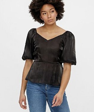 A woman wearing a Pieces black satin bell sleeve top with blue jeans.