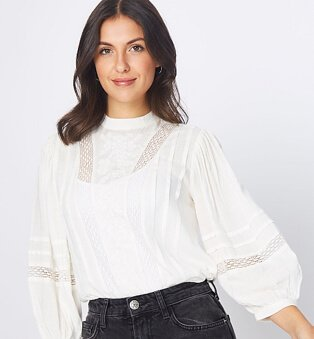 A woman wearing a cream ladder insert embroidered blouse with black jeans.