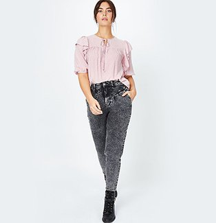 A woman wearing a pink bobble texture frill detail blouse with black acid wash jeans and black boots.