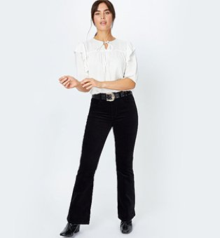 A woman wearing a white bobble texture frill detail blouse with black jeans and boots.