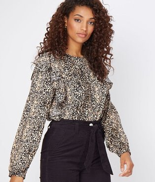 A woman wearing a leopard print frill shoulder blouse with black trousers.