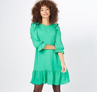 A woman wearing a green ruffle sleeve tiered dress with black tights.