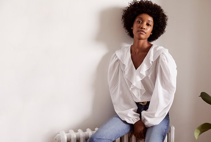 A woman sitting on a radiator wearing a white ruffle shirt with blue jeans.