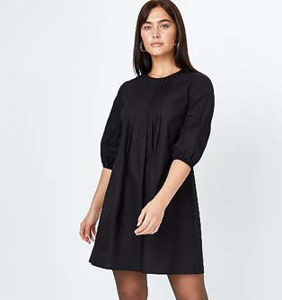 Woman poses wearing black pleated smock dress with ruched sleeves and gold-tone hoop earrings.