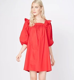 Woman poses wearing red balloon sleeve mini smock dress with frill shoulder detailing.
