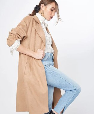 Woman poses side on raising one leg wearing cream high neck top, white checkered shirt, light wash blue jeans, tan faux suede belted throw-on jacket and gold-tone earrings.