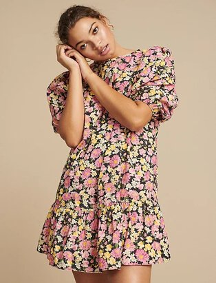 Woman poses resting head on hands wearing pink poplin floral balloon sleeve tiered mini dress and gold-tone hoop earrings.