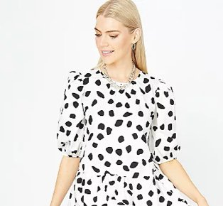 Woman poses looking to one side wearing white abstract spot print tiered poplin dress, silver-tone earrings and silver-tone chain necklace.