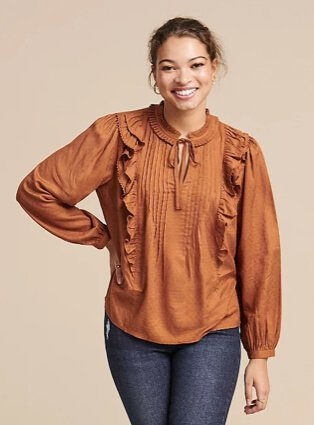 Woman poses smiling with hand on hip wearing tan textured frill tie-neck blouse and blue jeans.