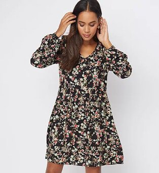 Woman poses with hands in hair looking down wearing black floral long sleeve smock dress.