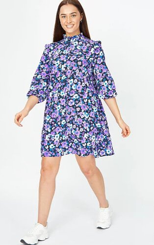 Woman poses smiling with one foot forward wearing purple floral print high neck dress and white trainers.